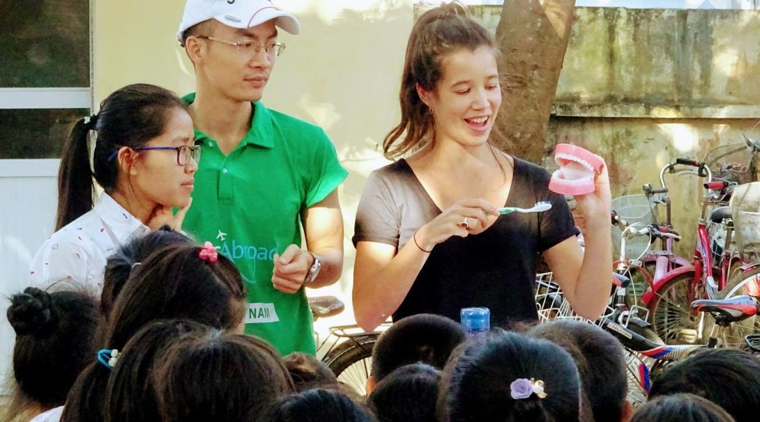 A group of Childcare volunteers teach a group of children how to brush their teeth at a care centre in Vietnam.